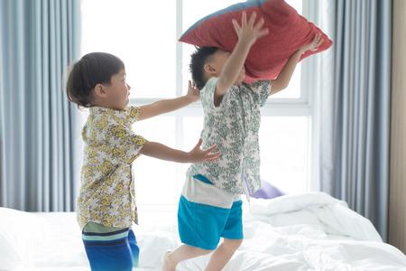 2 frères mignons sautent et jouent le matin sur le lit.