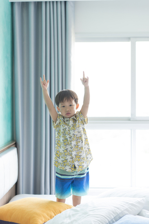 A boy is jumping and playing in the morning on the bed.