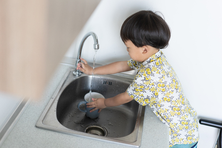 The boy is helping the mother to do the housework by washing a cup and a dish.