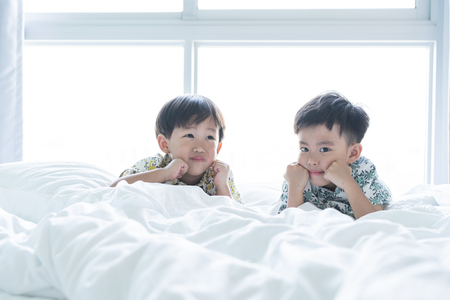 2 cute brothers are playing the morning on the bed.