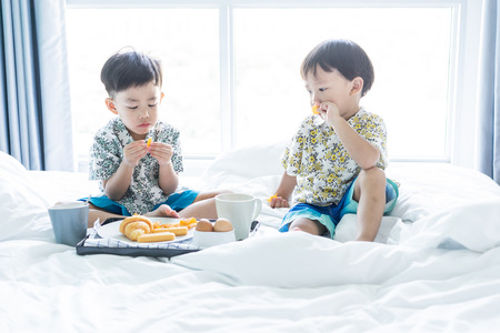 2 cute brothers are sharing breakfast on the bed in the morning.