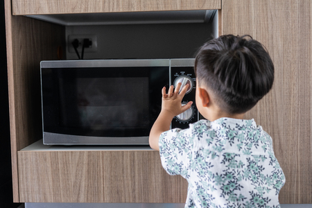 A boy is cooking his breakfast by microwave in kitchen in the morning 版權商用圖片
