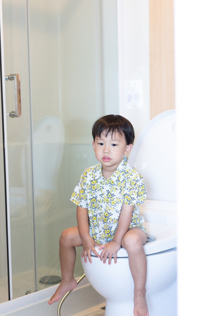 A boy is sitting on toilet with suffering from constipation or hemorrhoid. Stock Photo