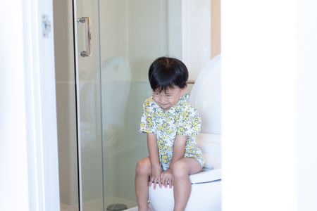 A boy is sitting on toilet with suffering from constipation or hemorrhoid. Stockfoto