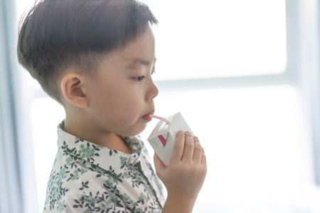 A boy is sucking milk from the milk box. He likes milk box so much. Stockfoto