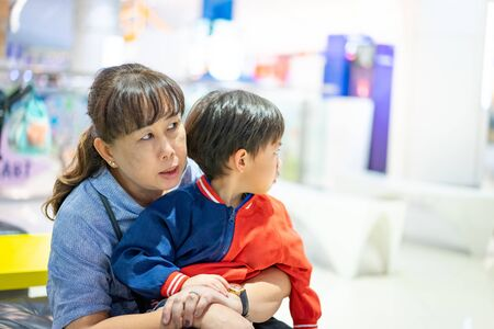 Grandson is crying, he want to buy toys at the department store. Grandma try to teach her grandson to understand why she can not buy its.