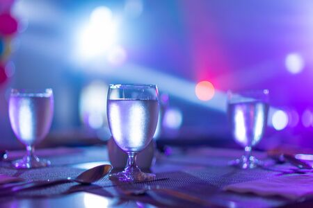 glass of water placed on the table In the restaurant with colorful light at night.