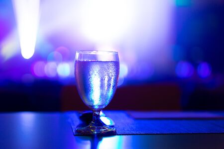 1 glass of water placed on the table In the restaurant with colorful light at night. 写真素材