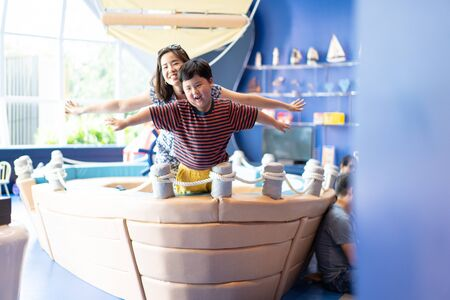 Mother and son are playing a boat together in the living room.