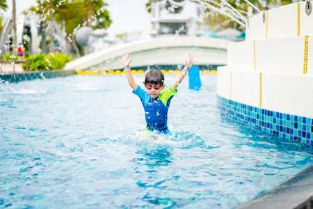 A boy is playing and swimming at the swimming pool in the evening.