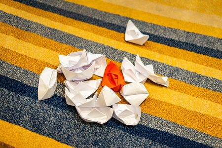 Paper boats are garbage on the carpet floor in the meeting room.