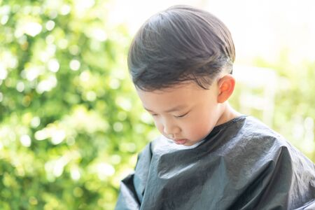 Grandma was cutting hair for her nephew at home in the garden during the day time.
