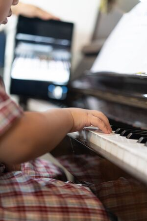 A boy is learning piano online with a tablet by the social network in his house.