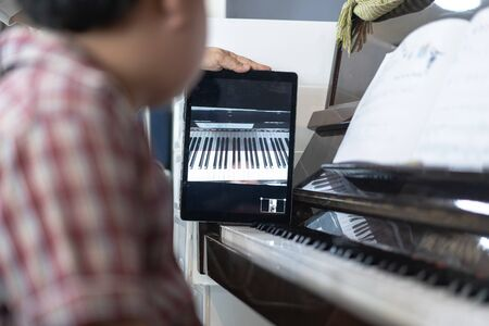 A boy is learning piano online with a tablet by the social network in his house. Archivio Fotografico