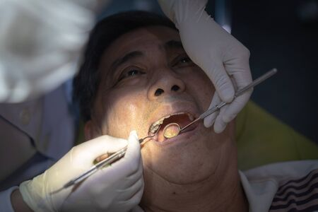 An Asian man having teeth examined at dentists: Healthy lifestyle, healthcare, and medicine concept. Foto de archivo