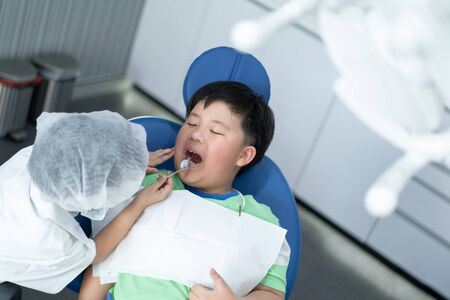 Little Asian dentist boy with a dentist suit try to check his patient teeth in the dentist clinic: Future career and career dream concept. Banque d'images