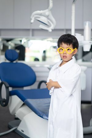 Little Asian doctor dentist boy with a dentist suit, standing in the dentist clinic: Future career and career dream concept.