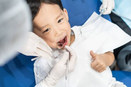 An Asian boy having teeth examined at dentists: Healthy lifestyle, healthcare, and medicine concept.