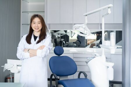 photo of a female dentist, standing in her dentist clinic.