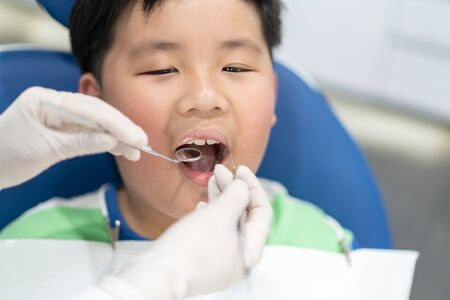 A fat boy having teeth examined at dentists: Healthy lifestyle, healthcare, and medicine concept.