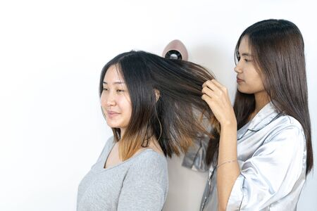 Photo of joyful Asian girl drying her friend's hair and having fun with sleeping suits.
