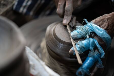 Close-up hands of a male potter. Artist is making a vase from clay, selective focus.