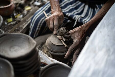 Close-up hands of a male potter. Artist is making a vase from clay, selective focus. Stock fotó