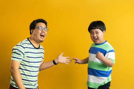 the rock-paper-scissors gesture of Asian father and child, successful cooperation of generations, yellow studio background