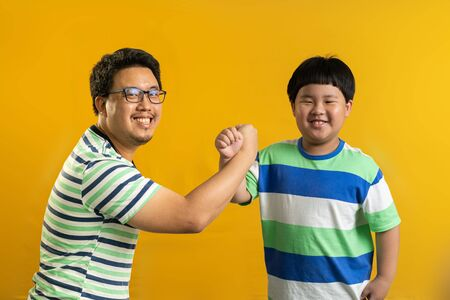 the cross-arm gesture of Asian father and child, successful cooperation of generations, yellow studio background