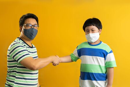 Shake hand gesture of Asian father and child, successful cooperation of generations, yellow studio background