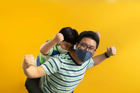 Small Asian son sits on strong dad shoulders showing biceps on yellow yellow background. Asian family enjoys activity games at home, a healthy fit lifestyle, two superheroes, happy Father Day concept. Banco de Imagens