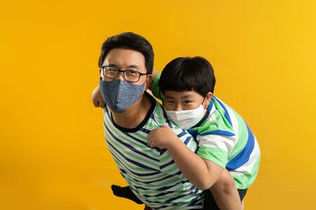 Asian father giving son ride on the back with a yellow background. Portrait of a happy father giving son piggyback a ride on his shoulders and looking up. Cute boy with dad playing indoor.