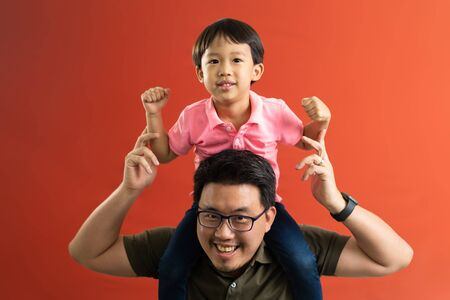 Asian father giving son ride on the back with a red background. Portrait of a happy father giving son piggyback a ride on his shoulders and looking up. Cute boy with dad playing indoor.