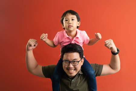 Small Asian son sits on strong dad shoulders showing biceps on red yellow background. Asian family enjoys activity games at home, a healthy fit lifestyle, two superheroes, happy Father Day concept. Banco de Imagens