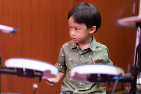 A boy is playing an electronic drum at the church. Stockfoto
