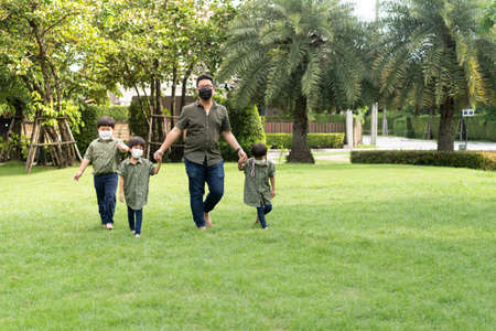 Father wears a mask, He is walking in the garden with his 3 sons.