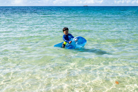 A boy is playing the sea and sand. A Little baby boy with inflatable toy float playing in the water on summer vacation in a tropical resort. Kid with toy dolphin on a beach holiday.