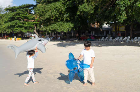 Brothers are playing the sea and sand. Little baby boys with inflatable toy float playing in the water on summer vacation in a tropical resort. Kids with toy shark and dolphin on a beach holiday.