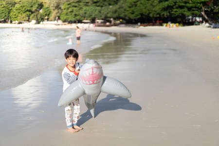 A boy is playing the sea and sand. A Little baby boy with inflatable toy float playing in the water on summer vacation in a tropical resort. Kid with toy shark on a beach holiday. 스톡 콘텐츠