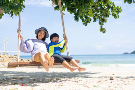 Mother playing on the swing with her children at the beach on holiday. 스톡 콘텐츠