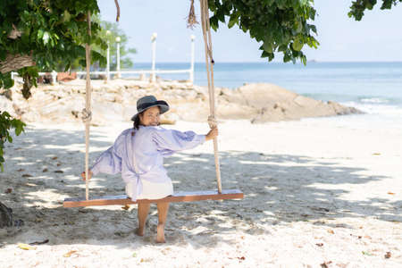 A woman is playing on the swing at the beach on holiday.