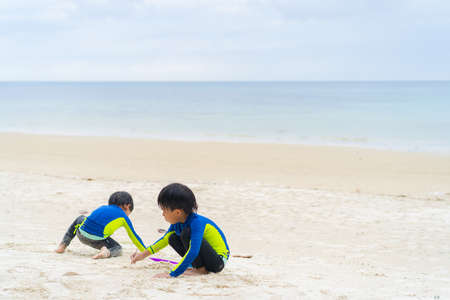 brothers are playing in the sand and swimming at the beach at an island in Thailand
