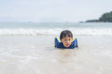 A boy is playing in the sand and swimming at the beach at an island in Thailand