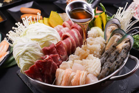 Shabu Shabu or Sukiyaki, a popular dish of pork, beef, shrimp, squid, seafood and fresh vegetables. Placed on a table with a boiling pot boiling in a Japanese restaurant. Standard-Bild - 157107475