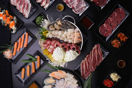 Shabu Shabu or Sukiyaki, a popular dish of pork, beef, shrimp, squid, seafood and fresh vegetables. Placed on a table with a boiling pot boiling in a Japanese restaurant. Stock Photo