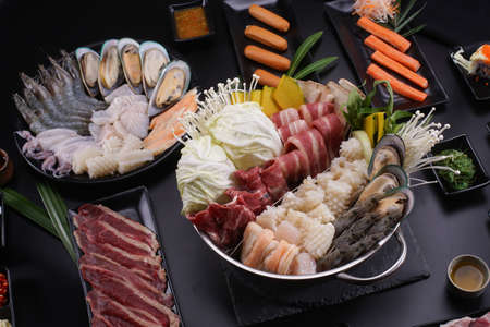 Shabu Shabu or Sukiyaki, a popular dish of pork, beef, shrimp, squid, seafood and fresh vegetables. Placed on a table with a boiling pot boiling in a Japanese restaurant. Standard-Bild - 157108127