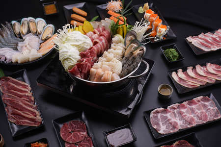 Shabu Shabu or Sukiyaki, a popular dish of pork, beef, shrimp, squid, seafood and fresh vegetables. Placed on a table with a boiling pot boiling in a Japanese restaurant. Standard-Bild - 157190399