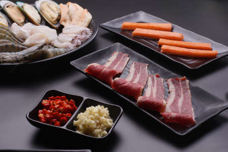 Raw beef slice and seafood for barbecue japanese style, yakiniku, meat are being cooked on stove in Japanese restaurant.