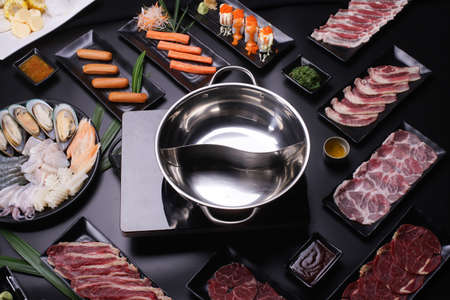Shabu Shabu or Sukiyaki, a popular dish of pork, beef, shrimp, squid, seafood and fresh vegetables. Placed on a table with a boiling pot boiling in a Japanese restaurant. Standard-Bild - 157107701