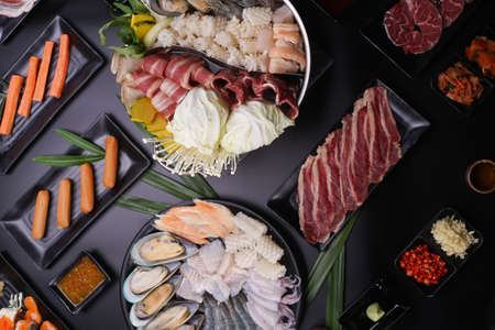 Shabu Shabu or Sukiyaki, a popular dish of pork, beef, shrimp, squid, seafood and fresh vegetables. Placed on a table with a boiling pot boiling in a Japanese restaurant. Standard-Bild - 157108341